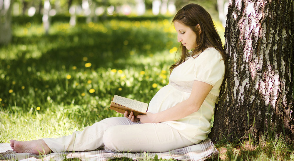 Beautiful pregnant woman in the park with book